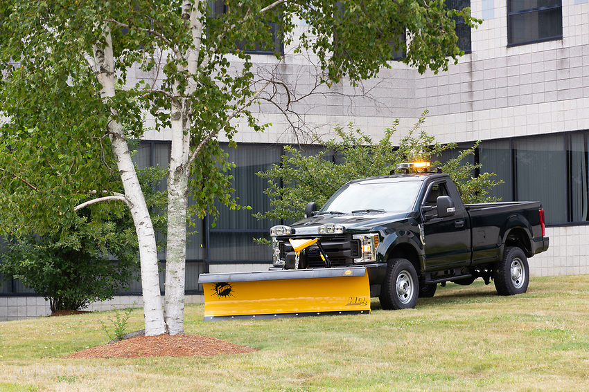 Black plow truck for public works with yellow plow and lights